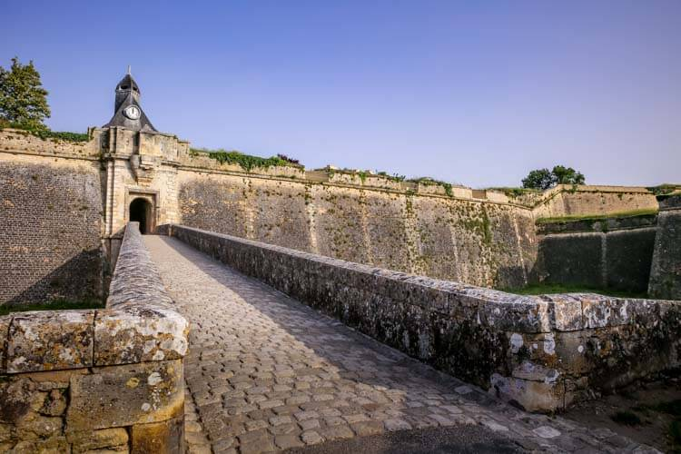 The stone path leading to Porte Dauphine with the clock tower rising above it at the Citadelle de Blaye