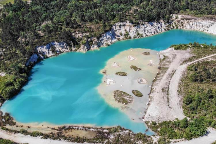 A drone aerial of Lac Bleu de Guizengeard showing the milky turquoise color of the water with some white clay islands and the lake surrounded by a pine forest