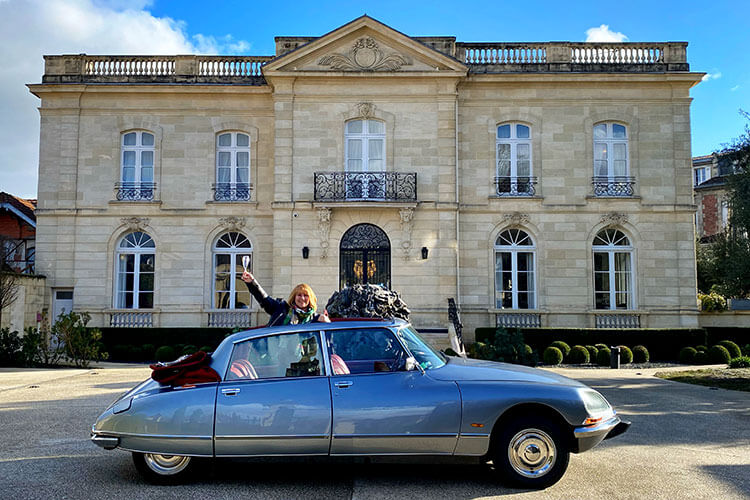 Jennifer poses in the Citroën DS with a glass of champagne and the top down in Bordeaux, France