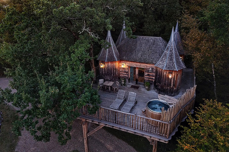 Drone view of Cabane Monbazillac tree house at dusk with lights on and the Nordic bath uncovered