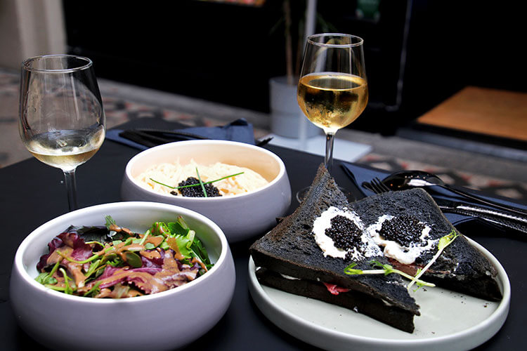 The table at Comptoir Caviar de Neuvic with lemon cream spaghetti and the black bread croque monsieur topped with caviar