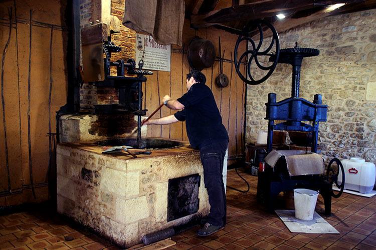 A worker stirs the dough as it heats in a large cast iron pot at the Ecomusée de la Noix
