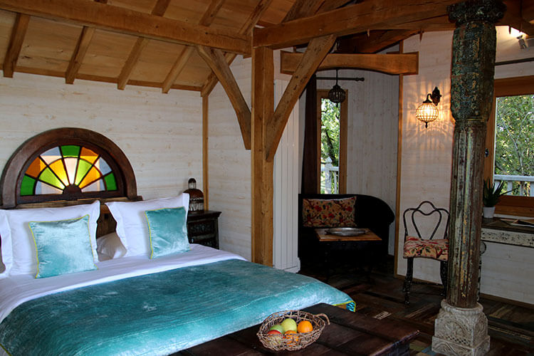 The bed with silk green linens in Cabane Monbazillac
