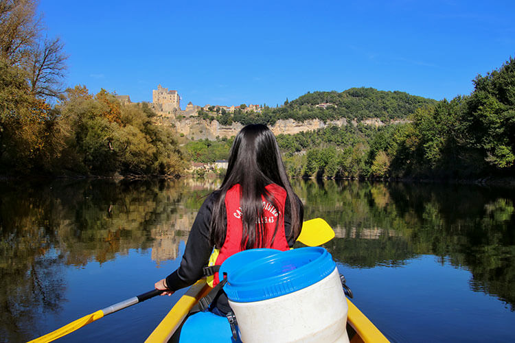 Jennifer's friend AJ paddling in the front of the canoe as a castle topped village reflects on the Dordogne River