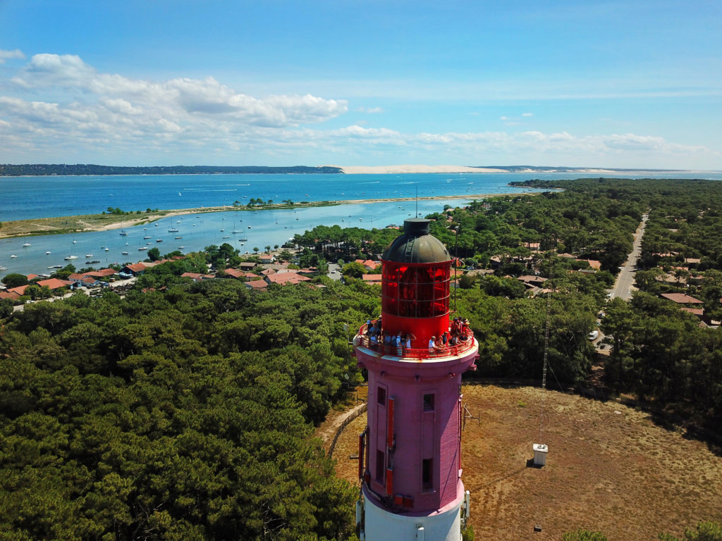 A drone aerial of the Cap Ferret Lighthouse with the Dune du Pyla visible across the bay