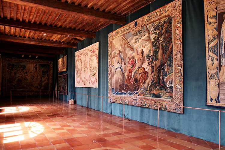 A collection of large tapestries is displayed in a room of Château de Vayres